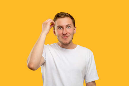 Surprised man portrait. Unexpected news. Excited guy with hand touching head isolated on orange background.