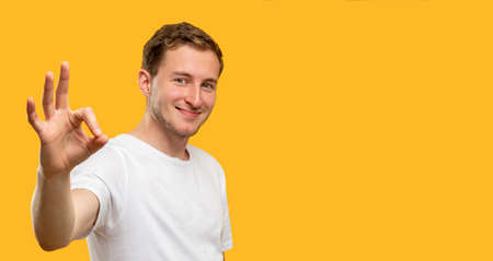 OK gesture. Ad background. Happy man showing approval sign isolated on yellow copy space.