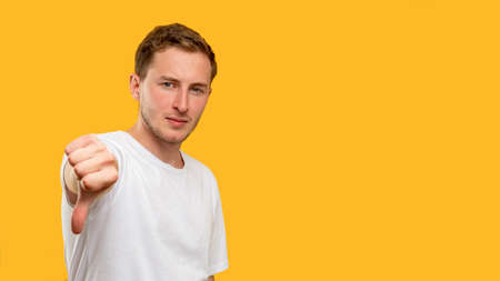Dislike gesture. Disapproval sign. Confident man showing thumb down isolated on orange copy space.