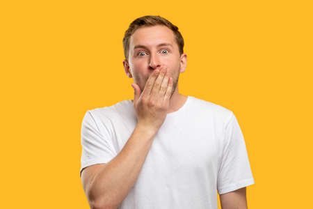 Amazed man portrait. Unexpected news. Shocked guy with hand covering mouth isolated on orange background.