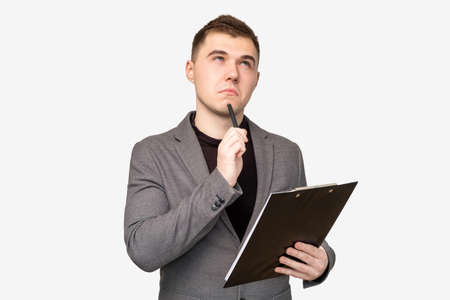 Startup idea. Marketing strategy. Pensive business man with clipboard thinking on project isolated on white.