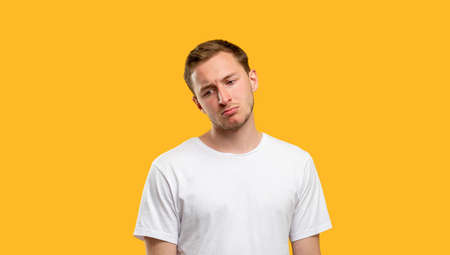 Sad man portrait. Failure disappointment. Upset guy in white t-shirt isolated on orange background.