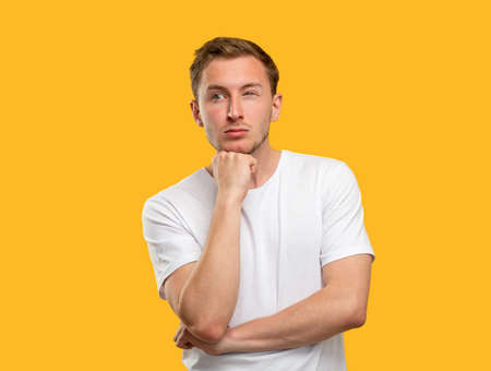 Puzzled man portrait. Tough decision. Concerned guy thinking on idea isolated on orange background. Standard-Bild