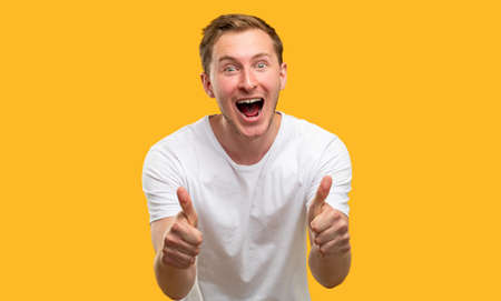 Like gesture. Approval admiration. Excited man supporting with thumbs up isolated on orange background. Reklamní fotografie