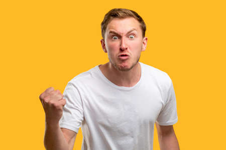 Angry man portrait. Warning gesture. Annoyed guy threatening with fist isolated on orange background. Reklamní fotografie