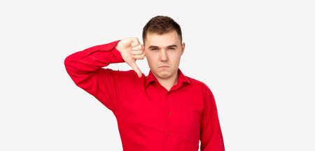 Dislike gesture. Bad idea. Skeptic man in red shirt showing thumb down isolated on white background. Reklamní fotografie