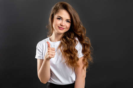 Like gesture. Achievement success. Confident woman showing thumb up isolated on gray background.