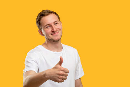 Like gesture. Support encouragement. Friendly man showing thumb up isolated on orange copy space background.