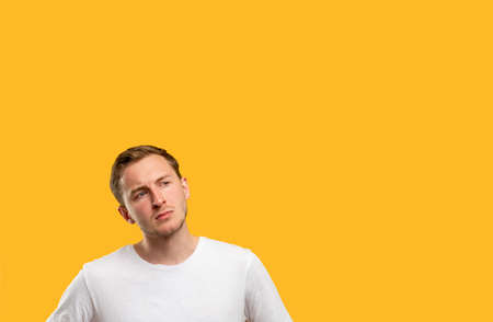 Curious man portrait. Promotional background. Pensive guy isolated considering offer on orange copy space.
