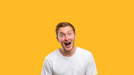 Wow portrait. Commercial background. Excited man with open mouth isolated on orange copy space.