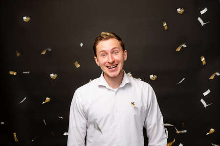 Birthday man portrait. Holiday surprise. Astonished guy smiling in confetti rain isolated on black background.