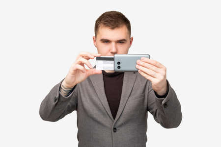 Mobile banking. Online payment. Confident business man using credit card smartphone isolated on white.