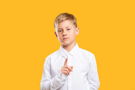Denial gesture. Attention signal. Confident boy in white shirt warning with finger isolated on orange background.