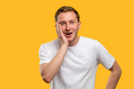 Wow portrait. Great news. Astonished man with hand on cheek open mouth isolated on orange background.