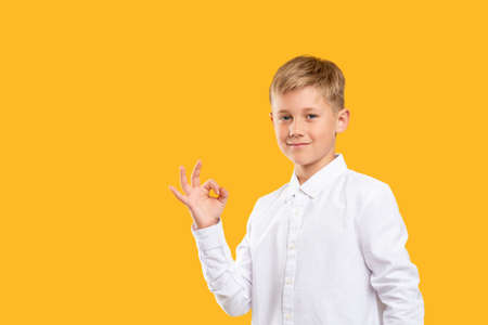 OK gesture. Deal agreement. Confident boy smiling showing approval hand signal isolated on orange copy space.