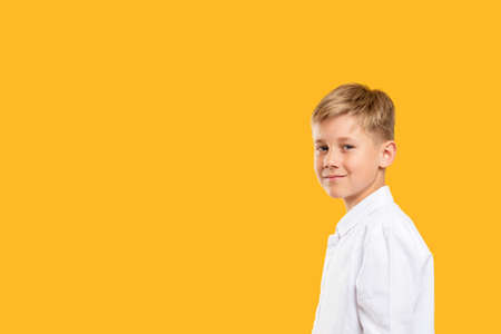 Confident child portrait. Back to school. Smart boy in white shirt smiling isolated on orange copy space.