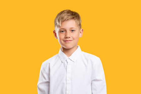 Happy kid portrait. Back to school. Confident blond boy in white shirt smiling isolated on orange background. Reklamní fotografie