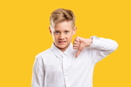 Dislike gesture. Failure disgust. Annoyed boy in white shirt showing thumb down isolated on yellow background.