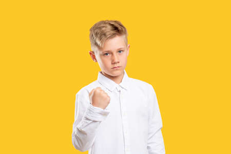 Angry boy portrait. Threat power. Confident aggressive kid warning with fist gesture isolated on yellow.
