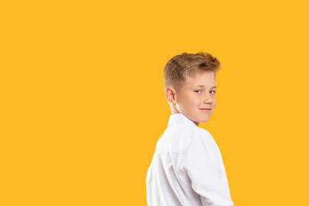 Confident kid portrait. Schoolboy lifestyle. Cheerful boy looking over shoulder isolated on orange copy space. Reklamní fotografie