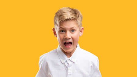 Scared child portrait. Panic attack. Frustrated boy in white shirt screaming isolated on orange background.