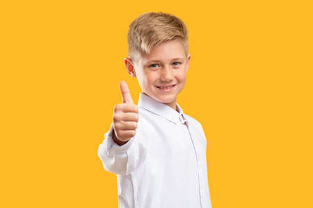 Like gesture. Schoolboy success. Confident boy in white shirt showing thumb up smiling isolated on orange. Reklamní fotografie