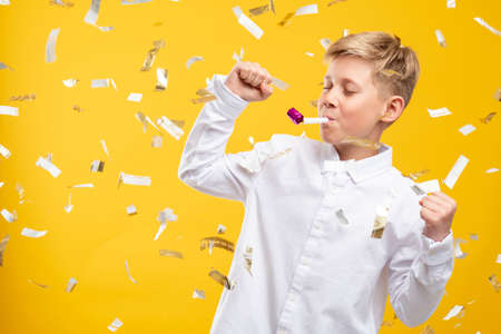 Birthday boy portrait. Festive joy. Happy kid dancing with party horn in confetti rain isolated on yellow.