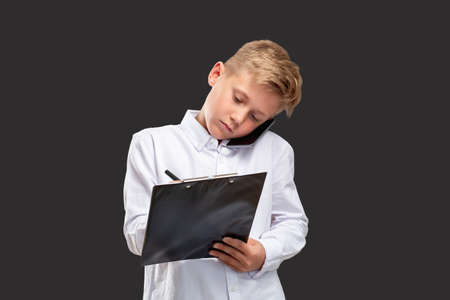 Kids in business. Professional career. Confident boy having phone call writing notes isolated on black. Reklamní fotografie
