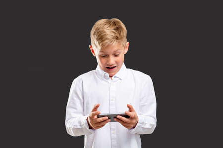 Mobile game addiction. Stress anxiety. Shocked boy losing playing on phone isolated on gray background.