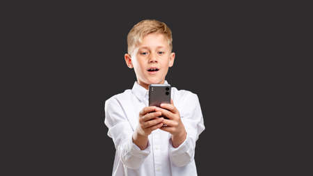 Online chat. Mobile app. Amazed boy in white shirt reading message on smartphone isolated on dark background.