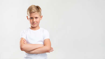 Confident boy portrait. Child lifestyle. Arrogant blond kid standing with crossed arms isolated on white copy space.