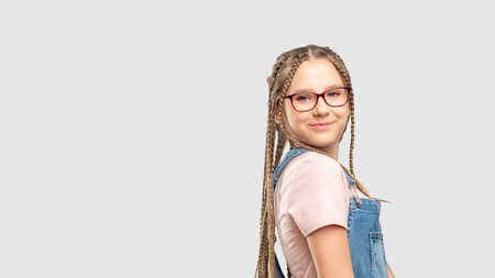 Kids eyewear. Eyesight correction. Happy girl in stylish eyeglasses smiling isolated on neutral copy space. Standard-Bild