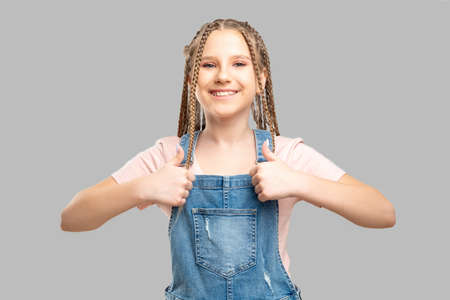 Happy child portrait. Like gesture. Cheerful girl showing thumbs up smiling isolated on neutral background. Stock Photo