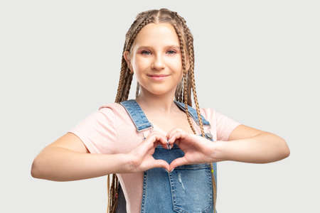 Love sign. Romantic message. Cheerful teen girl showing heart gesture isolated on neutral background.