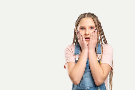 Amazed kid portrait. Special offer. Surprised girl touching cheeks isolated on white copy space.