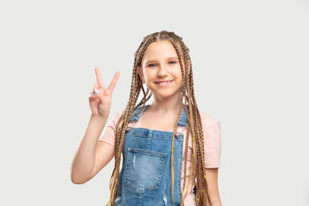 Peace gesture. Victory success. Cheerful girl showing two fingers smiling isolated on neutral background. Stock Photo