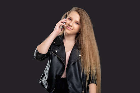 Teen lifestyle. Distance communication. Cheerful girl talking on phone smiling isolated dark background.