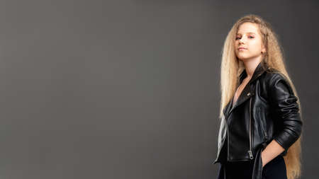 Stylish girl portrait. Commercial background. Confident young lady in biker jacket standing isolated gray empty space.