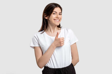 Like gesture. Perfect choice. Happy woman showing thumb up isolated on neutral background.