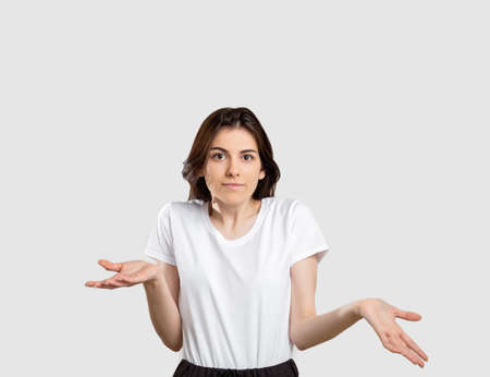 Shrug gesture. No idea. Confused woman raising shoulders isolated on neutral background.