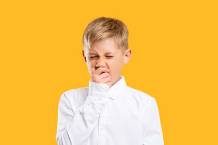 Tired kid portrait. Child lifestyle. Sleepy blond boy in white shirt yawning isolated on orange background.
