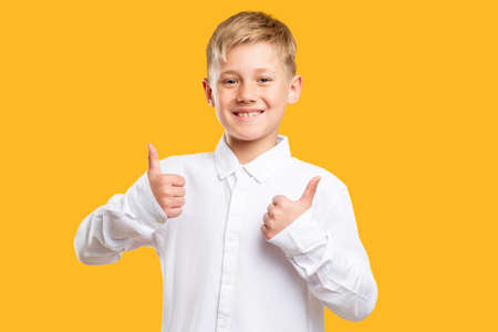 Like gesture. Approval sign. Cheerful boy in white shirt showing thumbs up isolated on orange background. Stock Photo