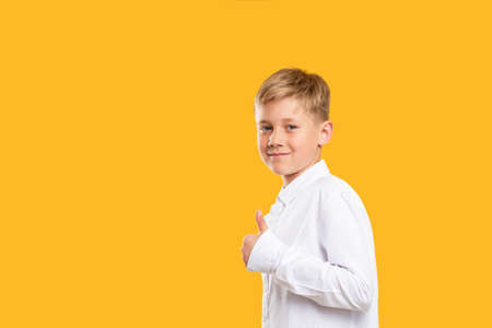 Like gesture. Commercial background. Friendly boy in white shirt showing thumb up isolated on orange copy space. Stock Photo