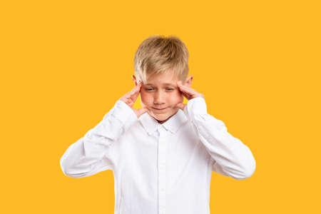 Child anxiety. Stress headache. Troubled boy in white shirt clutching head isolated on orange background.