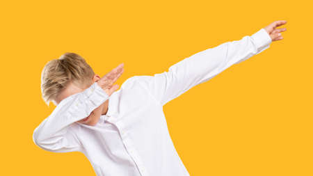 Dab gesture. Dance move. Amused boy raising arms dropping head in confident posture isolated on orange. Stock Photo