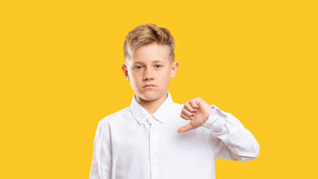 Dislike gesture. Loser shame. Dissatisfied boy showing thumb down isolated on yellow background.