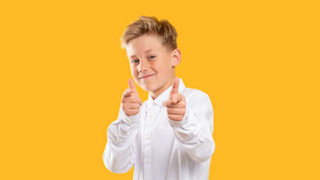 Encouraging gesture. Admiration support. Confident boy pointing fingers smiling isolated on orange background. Stock Photo