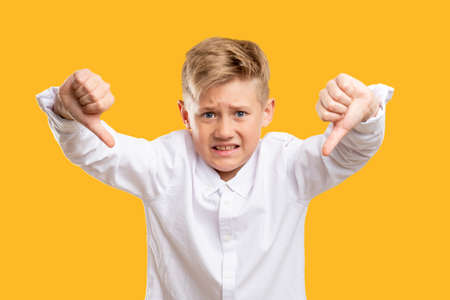 Dislike gesture. Awful idea. Dissatisfied boy in white shirt showing thumbs down isolated on orange. Stock Photo