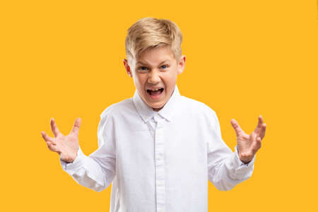 Angry child portrait. Child anxiety. Annoyed boy in white shirt yelling raising hands isolated on orange.