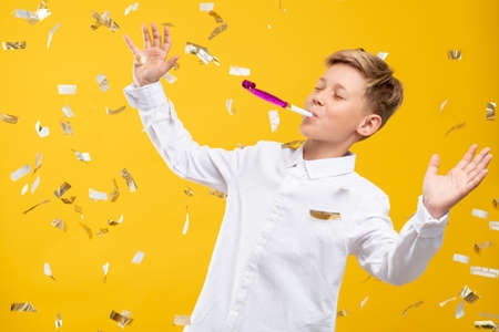 Birthday boy portrait. Fun celebration. Amused kid blowing party horn in confetti rain isolated on orange background. Stock Photo